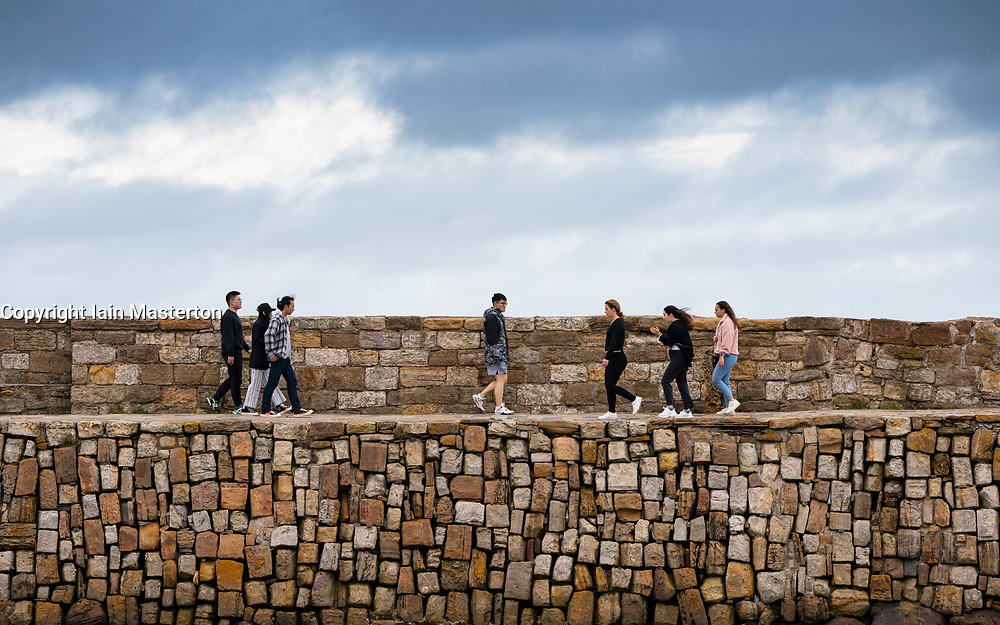 Students walking on harbour wall in St Andrews, Fife, Scotland, UK