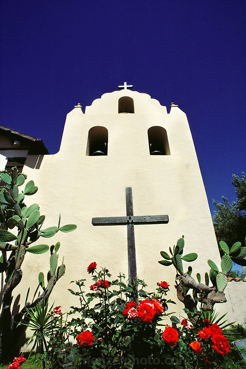 Campanile wall of Santa Ines Mission, Solvang, California, USA. with cactus, roses, and wooden cross.