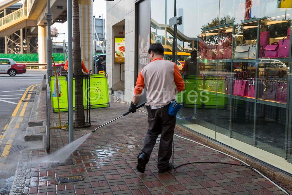 A worker power-washing the pavement outside a handbag shop in Hong Kong.