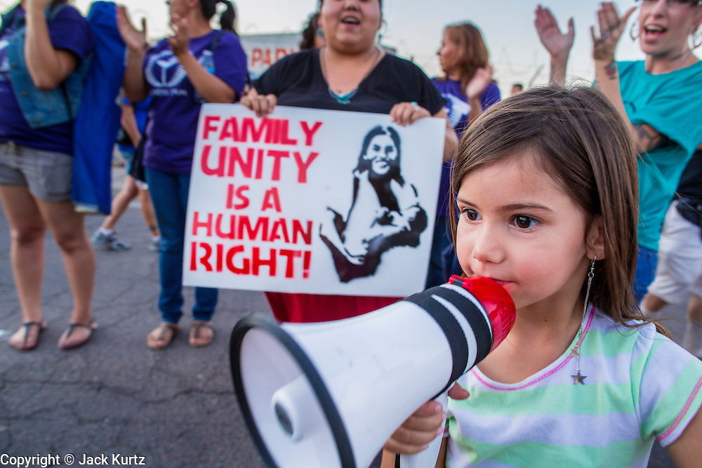 """23 JUNE 2012 - PHOENIX, AZ: A girl leads chants against Maricopa County Sheriff Joe Arpaio in front of the jail Saturday. About 2,000 members of the Unitarian Universalist Church, in Phoenix for their national convention, picketed the entrances to the Maricopa County Jail and """"Tent City"""" Saturday night. They were opposed to the treatment of prisoners in the jail, many of whom are not convicted and are awaiting trial, and Maricopa County Sheriff Joe Arpaio's stand on illegal immigration. The protesters carried candles and sang hymns.       PHOTO BY JACK KURTZ"""
