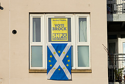 Edinburgh, Scotland, UK. 12th Dec 2019. Voting for the General Election takes place in the Edinburgh North and Leith constituency. A Pro SNP voter makes his voting intention clear with poster a flag in apartment window.  Iain Masterton/Alamy Live News