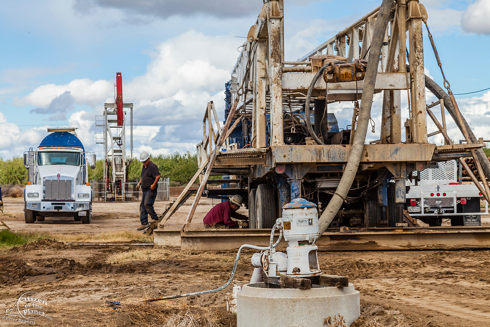 Water well being drilling next to oil well and fracking site in almond orchard. Kern County, located over the Monterey Shale, has seen a dramatic increase in oil drilling and hydraulic fracking in recent years. San Joaquin Valley, California, USA