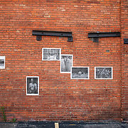 """""""Mira Mexico"""", newspaper exhibition installed on a wall in Rochester, New York June 30, 2013.<br /> (Credit Image: © Alysia Kaplan)<br /> <br /> Curator<br /> Alysia Kaplan (USA)<br /> <br /> Using photographs taken by Louie Palu relating to the Mexican drug war, this project challenges the reader to take apart this newspaper to see the full photographs and view the content. The goal is to force the reader to dismantle the vehicle used to deliver news and facts and thereby empower the reader to begin to think more critically. There are 16 photos in total, eight that do not relate to violence and eight that focus on violence or the drug business.. Each photograph is printed on a single sheet of newsprint, so if you take the newspaper apart each sheet of paper will have only one photograph on each side. Only eight pictures can be viewed at one time No photo can be entirely seen unless the reader opens and takes the newspaper apart. <br /> <br /> Once the newspaper comes apart it can be put back together in any order the reader wishes. The page spreads can also be hung as an exhibition. With violent images on one side and non-violent images on the other, the reader must become editor, curator or even censor, choosing how many violent photos are seen vs. how many non-violent photographs are seen. This forces the reader to face up to the fact that all delivery of news involves choices, of what to show and tell and what not to show and tell. It also forces the reader to face up to the system of institutions that serves as the gatekeepers in journalism and the visual arts. The questions are obvious. Is the editor censoring? Is the edit a true depiction of the news and the issue? Are violent images being used effectively to tell a story, or to sensationalize the story? The actual newspaper as an object forces the reader to engage in a a multidimensional exercise in journalism, art, and the politics of representation and message manipulation."""