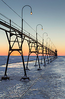 The setting sun leaves behind subtle tones of color on the frozen horizon of Lake Michigan.