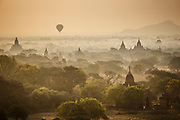 Balloons and mist rising over the temple plains of Bagan, Myanmar