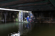 George W. Bush and Tony Blair are dragged into the water by the Devil. Satirical characters under a bridge on Regents Canal, London, UK.