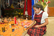 05 NOVEMBER 2004 - MEXICO CITY, MEXICO: A girl from a neighboring Catholic school lights a candle to Santa Muerte (St. Death) in Iglesia de la Piedad (Mercy Church) in the Tepito section of Mexico City. St. Death is venerated throughout Mexico and Mexican communities in the United States. The veneration of St. Death started in Mexico's prisons about 10 years and has since spread through working class neighborhoods in many Mexican cities. The worship St. Death was recognized as an official by the Mexican government in 2003. The Catholic Church in Mexico is opposed to the worship of St. Death and has held rallies and prayer vigils against the Saint. The small church in Tepito is frequently swamped with visitors and the religion has spread quickly through the tough, drug and crime plagued neighborhood, widely considered the most lawless in Mexico City.  PHOTO BY JACK KURTZ