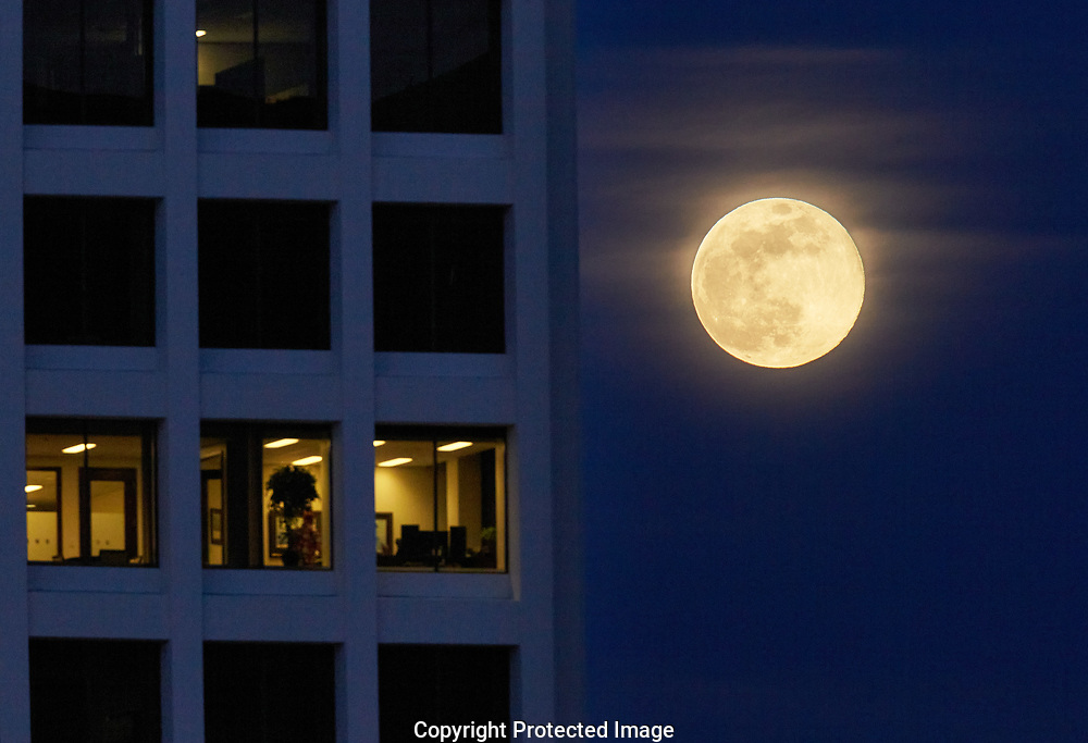 Supermoon behind a downtown building, Tuesday, April 7, 2020, in Tacoma. (Photo/John Froschauer)