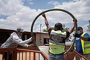 Coyote Canyon Chapter Secretary Sharon Tsosie assists Water Warriors Leon Curley and CB Barton with filling barrels at a residence near Coyote Canyon Chapter in the Navajo Nation near Gallup, New Mexico.