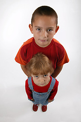 Wide angle portrait of boy with younger sister,
