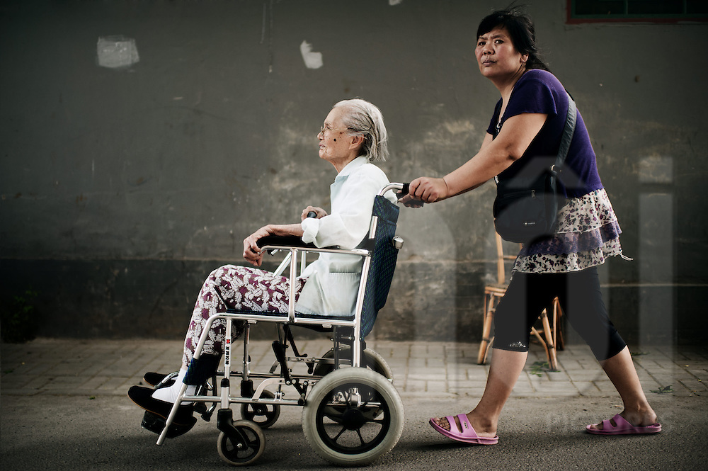 Elderly woman being pushed on a wheel chair through the old streets of Beijing, China