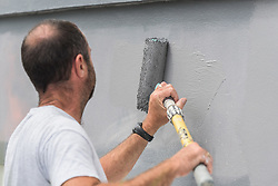 A painter and decorator paints the exterior wall of a house.