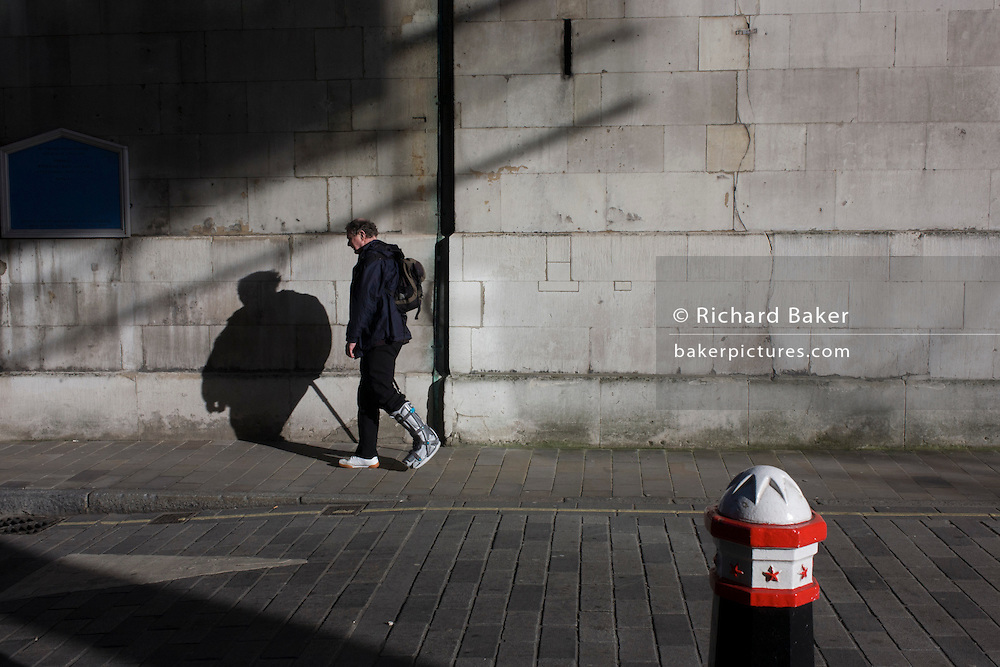 City of London bollard and businessman wearing a medical walking boot.