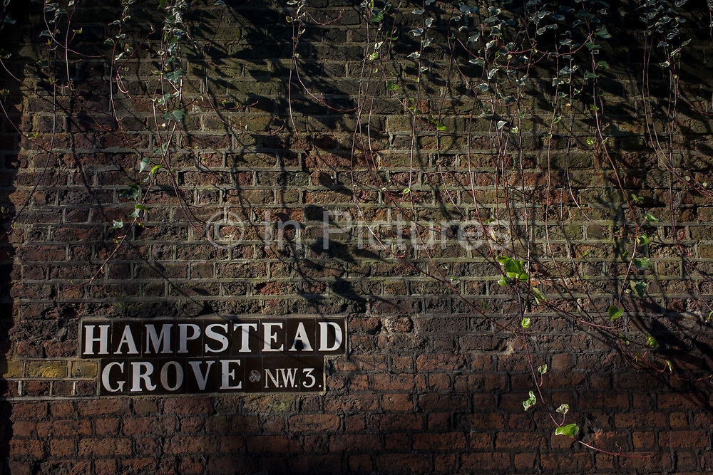 Detail of brick wall with Hampstead Grove NW3 road sign. Hampstead Grove is a street in London's Hampstead, District Camden with exclusive houses of great character, whose occupants have traditionally been of social and creative eminence. It runs between Lower Terrace to the north and Holly Hill in the south. In addition, Hampstead Grove meets the following streets: Upper Terrace to the north, Admiral's Walk in the middle and Windmill Hill in the south. The northern section of the road is flanked by green spaces. This area is called the Old Village Green. Here, by the year 1700, the parliamentary elections were Middlesex held. The green area was later used as a playing field for cricket used.