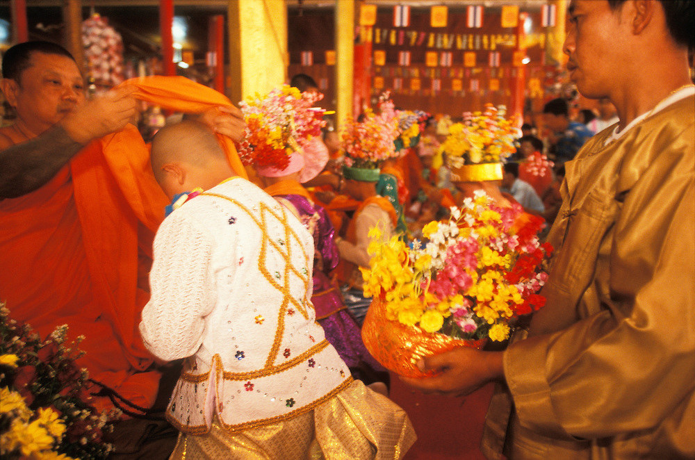 On the final day of the Poy Sang Long, the yearly ordination of novice monks, a monk passes the orange shirt over the head of a boy, a signal that he has become a novice monk and may now put on the rest of his orange robes, Mae Hong Son, Thailand. April 2003.