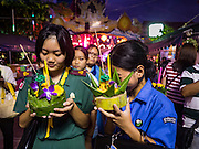 "25 NOVEMBER 2015 - BANGKOK, THAILAND:   Thai ""Girl Guides"" (Girl Scouts in the US) prays before floating their krathong in the Chao Phraya River during Loy Krathong at Wat Yannawa in Bangkok. Loy Krathong takes place on the evening of the full moon of the 12th month in the traditional Thai lunar calendar. In the western calendar this usually falls in November. Loy means 'to float', while krathong refers to the usually lotus-shaped container which floats on the water. Traditional krathongs are made of the layers of the trunk of a banana tree or a spider lily plant. Now, many people use krathongs of baked bread which disintegrate in the water and feed the fish. A krathong is decorated with elaborately folded banana leaves, incense sticks, and a candle. A small coin is sometimes included as an offering to the river spirits. On the night of the full moon, Thais launch their krathong on a river, canal or a pond, making a wish as they do so.    PHOTO BY JACK KURTZ"