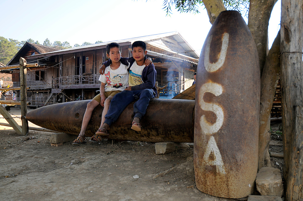 Two young boys in front of their home sit on bombs left over from the US and Vietnamese secret war in Phou Vieng, Laos.  The boy are sitting on a 2,000 lb. bomb.  The other bomb is a 750 lb. bomb.  The invading North Vietnamese Army destroyed the historic town in nearby Muang Sui.