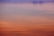 beautiful bright orange and purple tones washed over the calming and smooth ripples of the waters off British Columbia coastline photographed by tracie spence