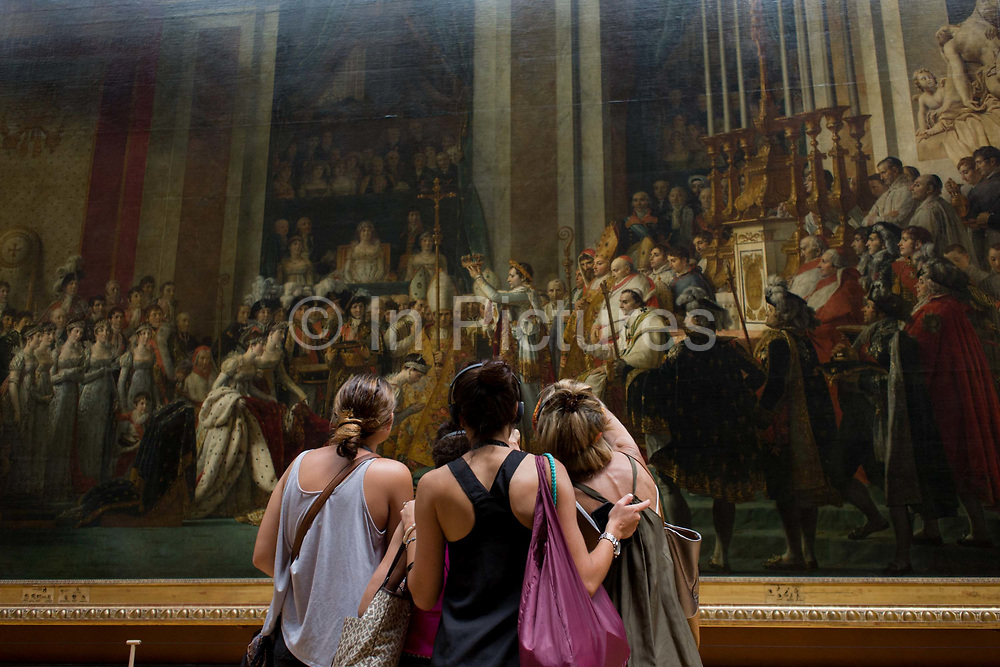 Three young women tourists admire The Coronation of Napoleon (Le Sacre de Napoléon), a painting of almost 10 x 6 metres completed in 1807 by Jacques-Louis David, the official painter of Napoleon. The crowning and the coronation took place at Notre-Dame de Paris, a way for Napoleon to make it clear that he was a son of the Revolution. The Musée du Louvre is one of the world's largest museums, the most visited art museum in the world and a historic monument. A central landmark of Paris, France, it is located on the Right Bank of the Seine in the 1st arrondissement (district). Nearly 100,000 objects from prehistory to the 19th century are exhibited over an area of 60,600 square metres (652,300 square feet).