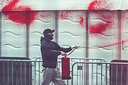 """An activist from the Palestine Action activist group is seen using an extinguisher with red paint spraying a security tent outside Abu Dhabi National Exhibition Centre Excel in East London on Sunday, Sept 12, 2021. Activists are targeting an arms fair hailed as """"the world's largest gathering of the defence and security community"""". (VX Photo/ Vudi Xhymshiti)"""