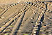 car tyre tracks in the sand on a beach