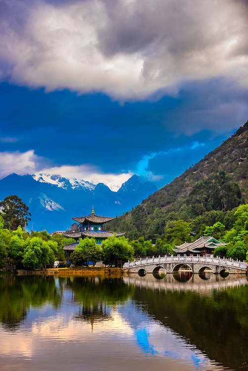 The idyllic Black Dragon Pool with the Deyue Pavilion  at the center and the  18,360 foot Jade Dragon Snow Mountain behind, Lijiang, Yunnan Province, China.