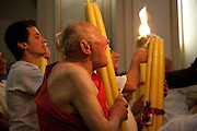 A man wearing only a traditional red sash on his upper body, carries a large devotional candle into church during the festival of Sant' Alfio at Trecastagni. Sicily, Italy.