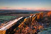Dawn warmth contrasts with the thick frost covering these jagged gritstone boulders below Stanage Edge. Overlooking Carhead Rocks & The Hope Valley. Kinder Scout is visible on the right side of the horizon. Peak District National Park, Derbyshire, England, UK. November, Autumn.
