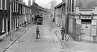 Soldiers on duty in the civilian-free streets during the curfew. 197007030251g. The British Army imposed during July 3 & 4, 1970, a 34 hour curfew (except for a two hour break to allow shopping) in approximately 50 streets in the Lower Falls district of Belfast, N Ireland, UK. A military helicopter hovered overhead warning people they would be arrested if they remained on the streets. An army search during the curfew uncovered 100 firearms, 100 home-made bombs, 250 lbs of explosives, 21000 rounds of ammunition and 8 two-way radios. This curfew is often seen as a turning point in souring relations between the Roman Catholic working class and the British Army. The army was no longer seen as the protector of the Catholic community.<br />