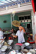 Cook at noodle restaurant throwing noodles into the air. Vung Tau, Vietnam