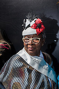New York, NY, USA-27 March 2016. Milliner Kathy Anderson wears one of her hats, in black and white leather, with a red leather poppy, on Fifth Avenue in the annual Easter Bonnet Parade and Festival. Ms. Anderson was there with a group from the Milliners Guild.