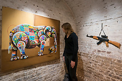 "© Licensed to London News Pictures. 24/05/2018. LONDON, UK. London, UK.  24 May 2018. An assistant views a painting of an African elephant at the preview of ""Missing"" an exhibition by artist and environmentalist Louis Masai at the Crypt Gallery in Euston.  The exhibition features sculptures, installations and paintings depicting 20 endangered species across the world from the South African penguin to the humble bumble bee.  The show runs 25 to 27 May 2018. Photo credit: Stephen Chung/LNP"