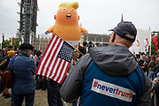 The stars and stripes upside down with the Trump Baby, a six metre high inflatable blimp flying above Westminster prior to protests against the state visit of US President Donald Trump on 4th June 2019 in London, United Kingdom. Organisers Together Against Trump which is a collaboration between the Stop Trump Coalition and Stand Up To Trump, have organised a carnival of resistance, a national demonstration to protest against President Trump's policies and politics during his official UK visit.