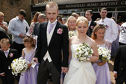 Bride and groom standing outside church with bridesmaids; ushers and guests,