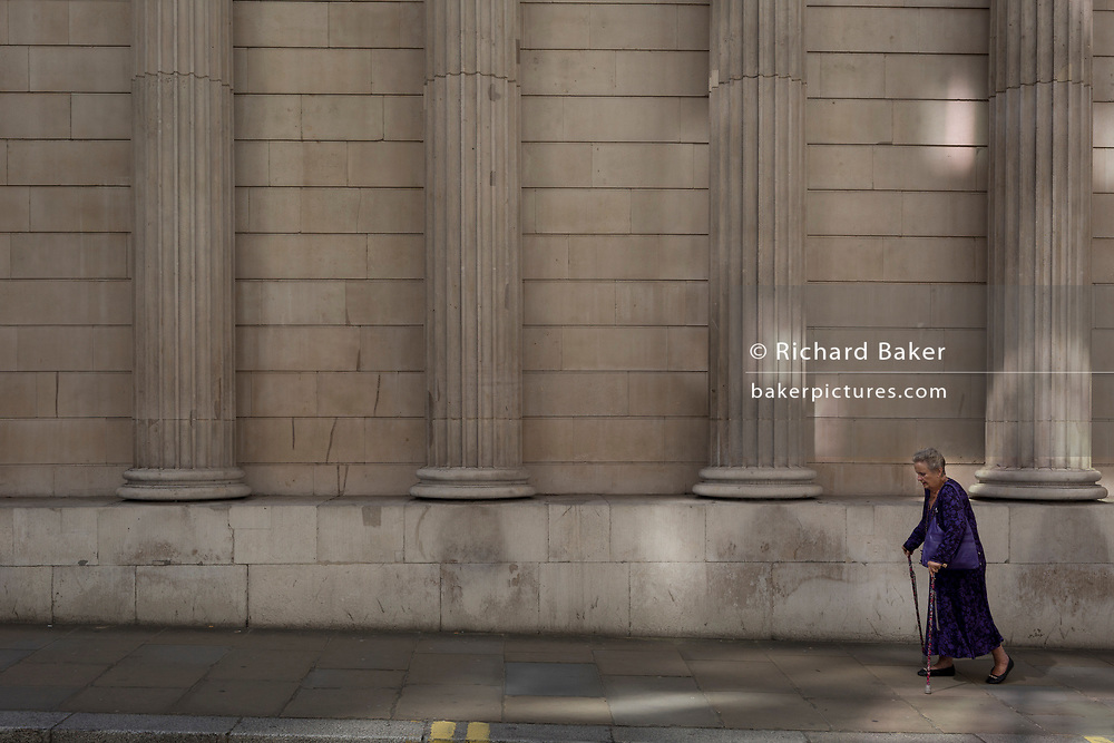 An elderly lady walks slowly beneath the pillars and columns of the Bank of England in Bartholomew Lane, in the City of London, the capital's financial district aka the Square Mile, on 15th May 2018, in London, UK.