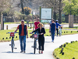 © Licensed to London News Pictures. 05/04/2020. London, UK. A couple push their bikes in Richmond Park after cycling was banned. Members of the public come out to exercise as temperatures reach 21c this weekend. Richmond Park seems quieter after the Government urged the public not to leave home during the fine weather as the Coronavirus crisis continues. Photo credit: Alex Lentati/LNP