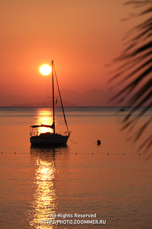 Yacht silhouette in Aegean sea over sun and mountains, Turkey