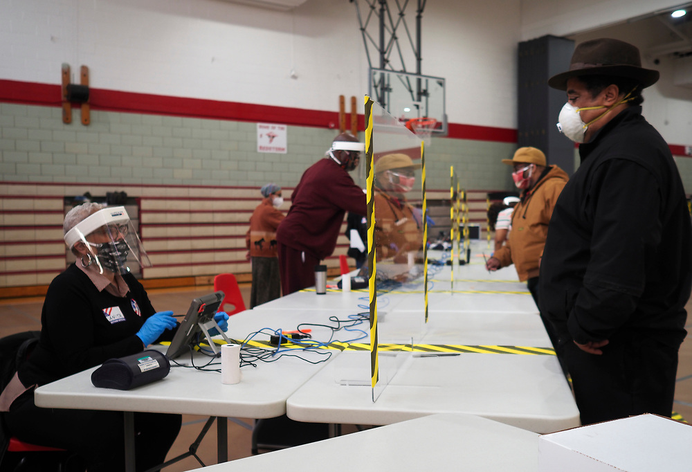 A poll worker wearing protective gear works behind a plastic shield as she checks in a voter at a voting center in Baltimore. On April 28, 2020 a special election was held to fill the remainder of the term in the US House of Representatives for Maryland's 7th congressional district. Elijah Cummings, the incumbent representative, died in office on October 17, 2019.