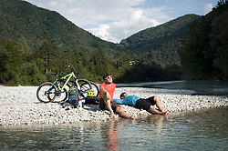 two mountain bikers having a rest at Soca river, Tolmin, Istria, Slovenia