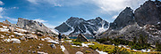 """On the Continental Divide Trail below Temple Pass, see Temple Lake in Bridger Wilderness, Wind River Range, Bridger-Teton National Forest, Rocky Mountains, Wyoming, USA. At left is the sharp point of East Temple Peak. The Continental Divide follows the crest of the """"Winds"""". We backpacked to Big Sandy Lake Campground (11 miles round trip with 1000 feet gain). A great day hike took us from Big Sandy Lake to Clear Lake and Deep Lake below East Temple Peak then loop back via Temple Lake, Miller Lake, and Rapid Lake (7.5 miles, 1060 ft gain) on the Continental Divide Trail. Mostly composed of granite batholiths formed deep within the earth over 1 billion years ago, the Wind River Range is one of the oldest mountain ranges in North America. These granite monoliths were uplifted, exposed by erosion, then carved by glaciers 500,000 years ago to form cirques and U-shaped valleys. This image was stitched from multiple overlapping photos."""