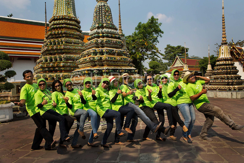 Muslim workers from an insurance company all dressed in branded Tshirts pose for a group shot inside the temple of Wat Pho in Bangkok, Thailand.