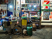 24 FEBRUARY 2016 - BANGKOK, THAILAND:  A sidewalk coffee vendor waits for customers in front of a 7/11 at Pak Khlong Talat in Bangkok. Bangkok government officials announced this week that vendors in Pak Khlong Talat, Bangkok's well known flower market, don't have to move out on February 28. City officials are trying to clear Bangkok's congested sidewalks and they've cracked down on sidewalk vendors. Several popular sidewalk markets have been closed in recent months and the sidewalk vendors at the flower market had been told they would be evicted at the end of the month but after meeting with vendors and other stake holders city officials relented and said vendors could remain but under stricter guidelines regarding sales hours. The flower market is one of the best known markets in Bangkok and has become a popular tourist destination.       PHOTO BY JACK KURTZ