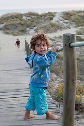 Portrait of a small child standing on boardwalk at the beach, Viana do Castelo, Norte Region, Portugal