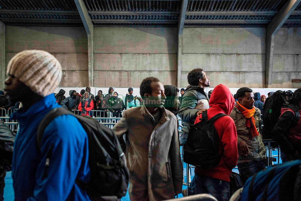 October 24, 2016 - Calais, France - Inside of the warehouse, migrants are waiting to receive a bracelet of a specific colour which will determine the place of the center in Calais, France, on 24 October 2016. One third of the migrants living in the Jungle was today registered and dispatched vias various regions of the French territory. They were asked to queue in front of a warehouse where they were given a bracelet with a specific colour. They eventually got into their allocated bus. (Credit Image: © Guillaume Pinon/NurPhoto via ZUMA Press)