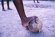 A ragged, bare football in a Rio de Janeiro favela, Brazil.