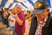 """13 JULY 2012 - FT DEFIANCE, AZ: Veterans line up for a special alter call during the veterans' service Friday night at the 23rd annual Navajo Nation Camp Meeting in Ft. Defiance, north of Window Rock, AZ, on the Navajo reservation. Preachers from across the Navajo Nation, and the western US, come to Navajo Nation Camp Meeting to preach an evangelical form of Christianity. Evangelical Christians make up a growing part of the reservation - there are now more than a hundred camp meetings and tent revivals on the reservation every year. The camp meeting in Ft. Defiance draws nearly 200 people each night of its six day run. Many of the attendees convert to evangelical Christianity from traditional Navajo beliefs, Catholicism or Mormonism. """"Camp meetings"""" are a form of Protestant Christian religious services originating in Britain and once common in rural parts of the United States. People would travel a great distance to a particular site to camp out, listen to itinerant preachers, and pray. This suited the rural life, before cars and highways were common, because rural areas often lacked traditional churches.  PHOTO BY JACK KURTZ"""