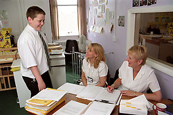 Young patient talking to healthcare assistant and receptionist in reception area of community paediatric health centre,