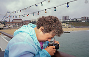 A lady peers down into the viewfinder of a vintage film camera whilst holidaying on the pier at Bournemouth seaside resort, on 20th October 1990, in Bournemouth, England.