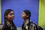 Before lessons begin, Poonam, 12, (left) and her sister Jyoti, 13, (right) are standing on the street facing the cozy, private school they regularly attend since 2011, located by their newly built home in Oriya Basti, one of the water-contaminated colonies in Bhopal, central India, near the abandoned Union Carbide (now DOW Chemical) industrial complex, site of the infamous '1984 Gas Disaster'. The two girls are studying in Year 6, out of 12, in 2015-16.