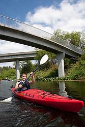 North America, United States, Washington, Bellevue, teenage boy kayaking under highway bridge in Mercer Slough Nature Park.  MR